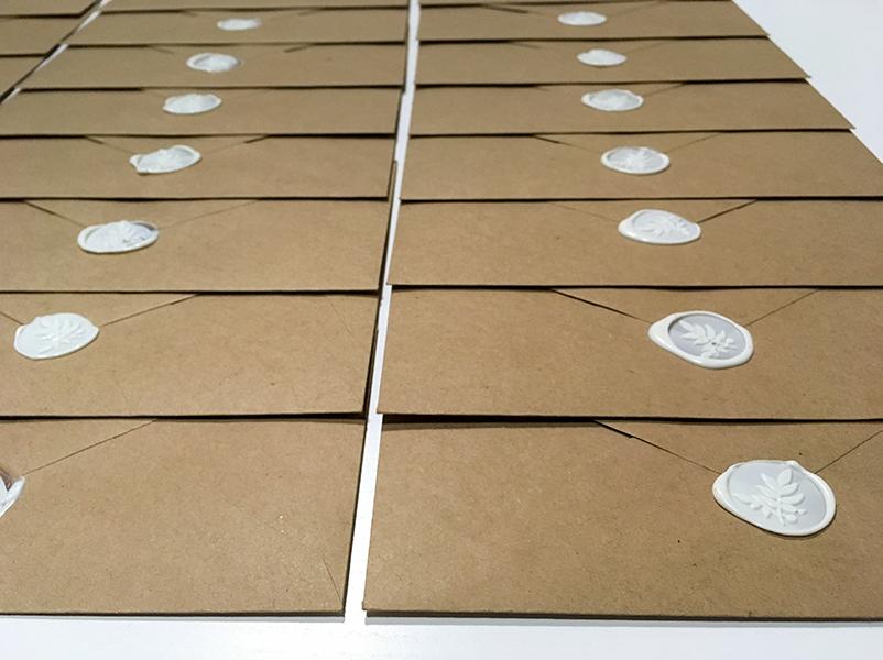 coordinato grafico matrimonio: fila di buste marroni con sigillo in cera bianco