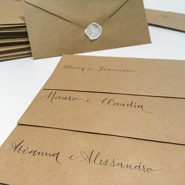 coordinato grafico matrimonio: buste marroni con nomi scritti a mano con tecnica calligrafica e timbro in cera bianco